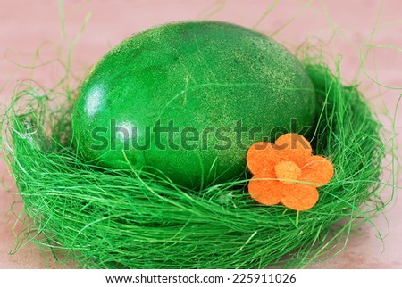 one colored green Easter egg in decorative nest - stock photo