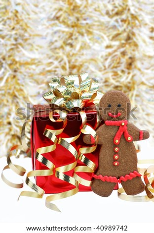 One colorful gingerbread man cookie with a red scarf standing next to a red Christmas gift.