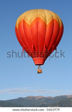 One colorful hot air balloon with the Rocky Mountains as backdrop during an early morning ascend - stock photo