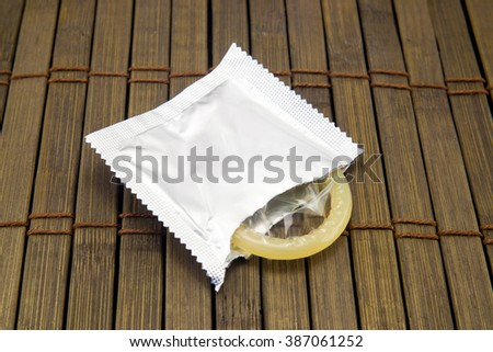 One condom on wooden background. Stock image - stock photo