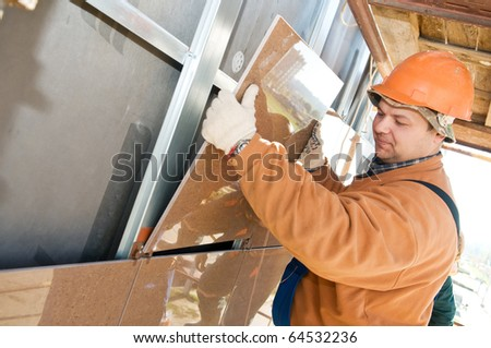 One construction worker builder installing big tile on a building facade - stock photo