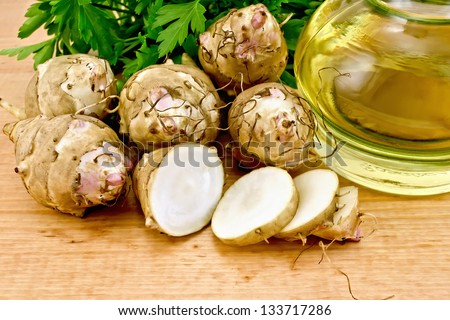 One cut and a few whole tubers of Jerusalem artichoke, parsley and a bottle of vegetable oil on a wooden board - stock photo