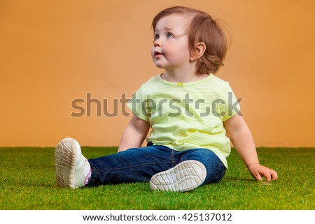 One cute and funny baby girl on orange background - stock photo