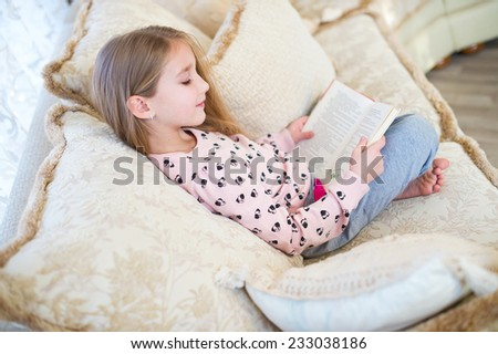 One cute toddler european girl with long blond hair reading book on sofa in the room at home - stock photo
