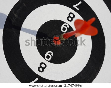One dart is hitting perfectly on the black dart board - stock photo