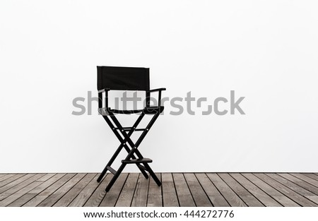 One Director Chair on wood floor and white wall - stock photo