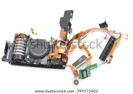 One disassembled digital camera with exposed lens and green soldered board against a white background - stock photo