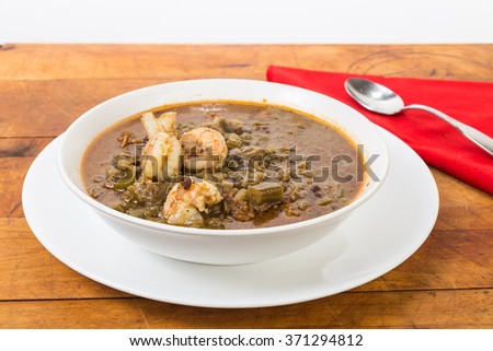 One dish Cajun meal of spicy shrimp gumbo with red beans and rice.  Soul food on Rustic wood tabletop with spoon and red napkin. - stock photo