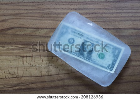 One dollar bill frozen in ice. - stock photo