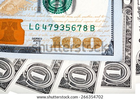 One dollar bills and hundred dollar (new design) banknote macro photo. - stock photo