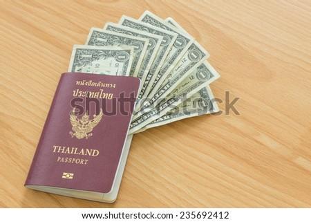 one dollar bills in thai passport - stock photo