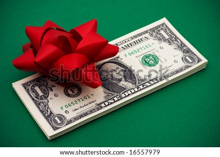 One dollar bills with red bow on it on green  background, gift of money