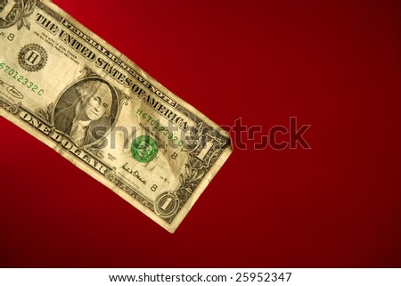 One dollar note over red background, studio crop shot - stock photo