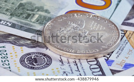 One dollar silver American eagle coin over bank notes background
