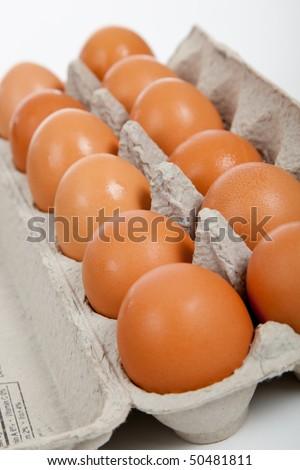 One dozen of brown eggs in a gray carton on white - stock photo