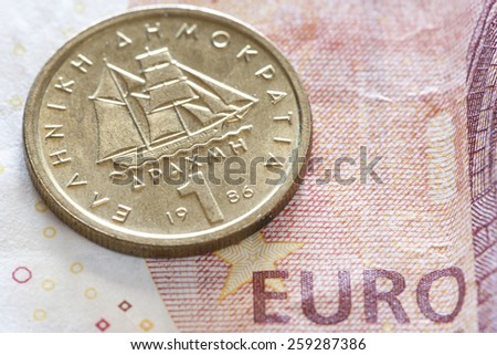 One drachma Greek coin on Euro notes. Selective focus. - stock photo