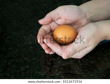 One egg nestled protectively in two hands over black granite counter.