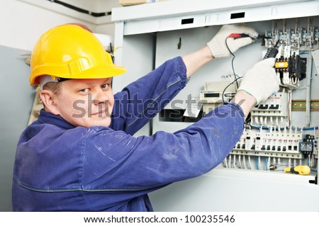 One electrician builder at work with tester measuring high voltage of power electric line in distribution fuseboard with multimeter - stock photo
