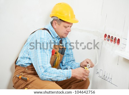 One electrician worker at wiring cable and light switch or power wall outlet socket installation work - stock photo