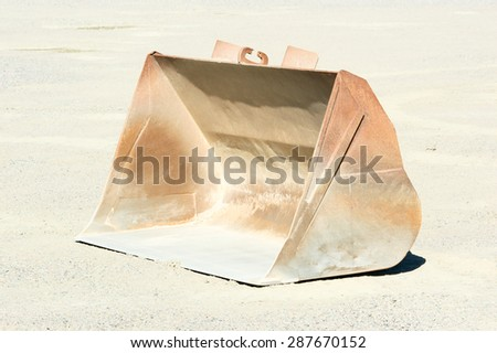 One empty loading bucket left in gravel pit after use. - stock photo