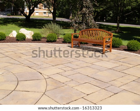 one empty wood bench by a stone patio - stock photo