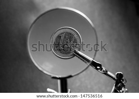 One euro cent in clip over magnifier lens. Finance concept. - stock photo