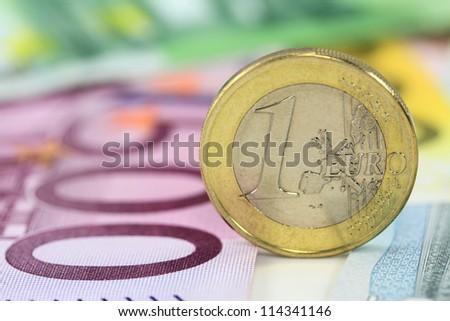 One euro coin against euro banknotes. Shallow DOF on euro coin - stock photo