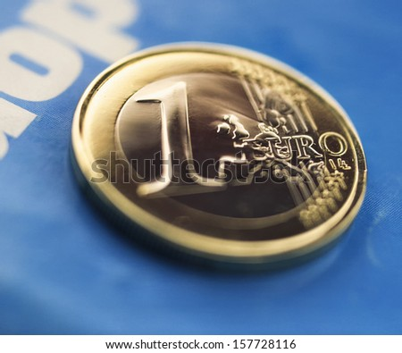 one euro coin against the background of blue paper closeup - stock photo