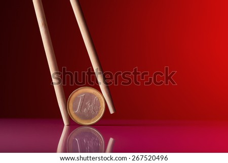 One euro coin and chopstick over red background - stock photo
