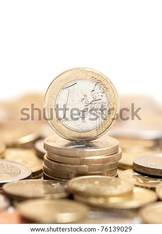 one euro coin on pile of other coins in background