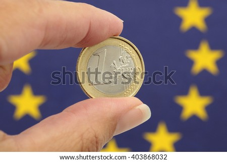 One euro in front of the European flag - stock photo