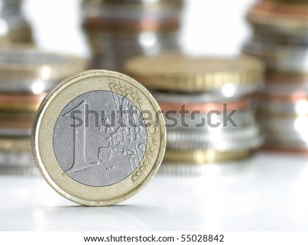 One euro money coin , closeup with stacks of coins in the background, shallow DOF, useful for various economy or financial themes - stock photo