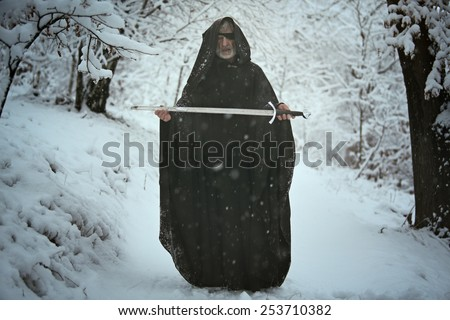 One eyed mysterious old man offering a sword in snowy forest . Myth and fantasy - stock photo