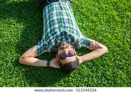 One fashion middle eastern man with beard, fashion hair style is resting on beautiful green grass day time. young arab businessman 20-30 years, resting after hard work. smart phone, tablet. looking  - stock photo