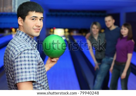One fellow stands sideways and holds ball for playing in bowling and three friends hearten him, focus on  man - stock photo