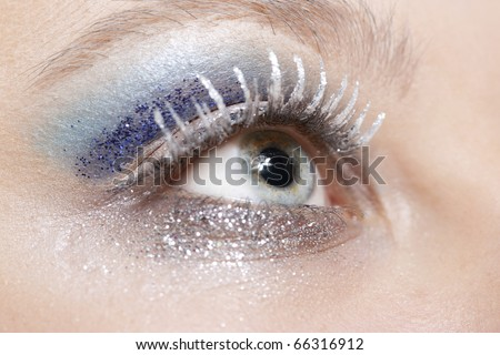 One female eye with blue eyeshadow and silver sparkle make-up - stock photo