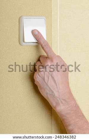 One finger switching, in or off, the light with a big square security electric interrupter - stock photo