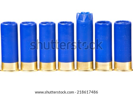 One fired shotgun shell among unused ammo isolated on white - stock photo