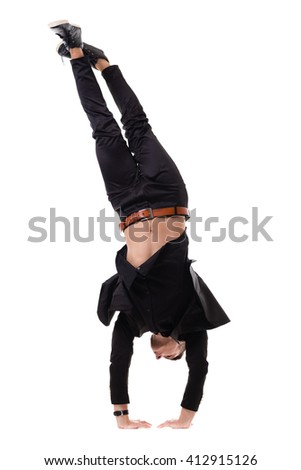 One fit handsome modern style dancer young man working out, performing breakdance moves, hand stand on the floor.
