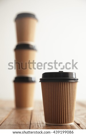 One focused cardboard paper cup in front of three take away cups with black caps standing in column on rustic vintage table isolated on white - stock photo