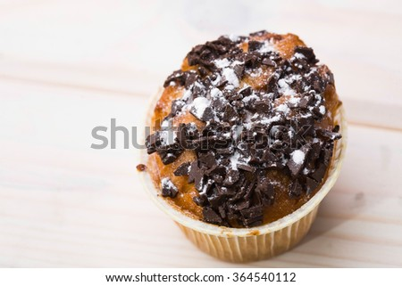 One fresh delicious muffin decorated by chocolate and powdered sugar fattening meal unhealthy food pastries carbohydrates studio on light background top view closeup copyspace, horizontal picture  - stock photo