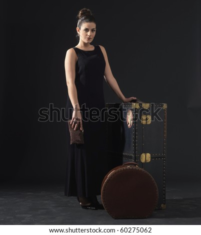 One front view of a beautiful woman dressed in retro style next to old luggage. - stock photo