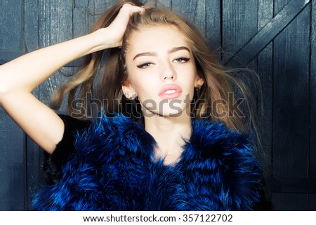 One funny young fashionable pensive sensual woman with beautiful long curly hair in waist coat of blue fur standing in hairdressing saloon in studio on wooden background, horizontal picture