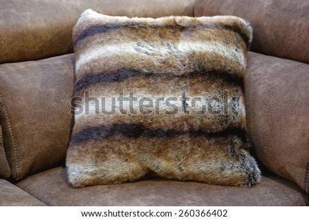 One furry decorative pillow at sofa - stock photo