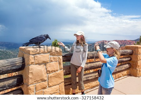 One girl reaches out to the crow and the other photographs.,  Bryce Canyon National Park, Utah, USA - stock photo