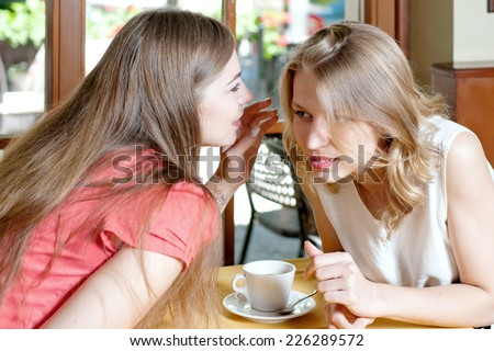 One girl whispers in the ear of another a secret - stock photo