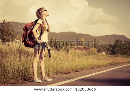 one girl with backpack walking on the road - stock photo