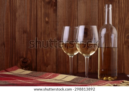 One glass bottle and two bocals full of white wine standing close to each other on checkered plaid on brown wooden wall background copyspace, horizontal picture - stock photo