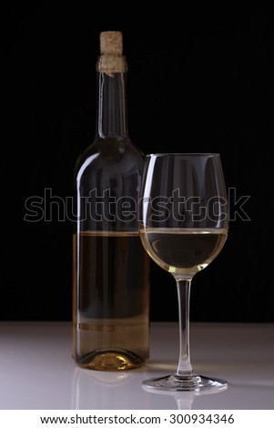 One glass bottle withcork and goblet of white wine standing on flat table top isolated on black studio background, vertical picture - stock photo