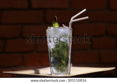 One glass goblet with alcoholic mojito cocktail of light cuban rum fresh lime juice fresh mint leaves granulated sugar soda water and ice cubes and drink straw on brick background, horizontal photo - stock photo